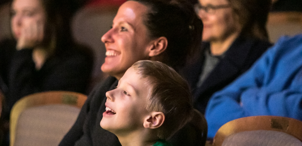 A woman and a child enjoy a show