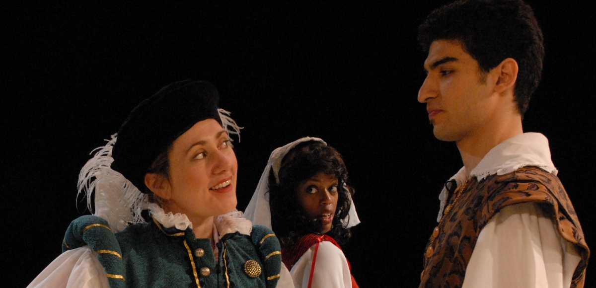 Rosalind in turquoise vest, white shirt and black hat with white feather; Celia in white veil, Orando in white shirt and brown figured doublet.