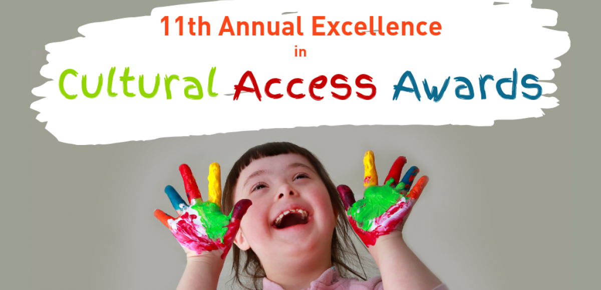 "11th Annual Excellence in Cultural Access Awards, happy girl with Down Syndrome with paint on hands has painted ""Cultural Access Awards"" in bold colors"
