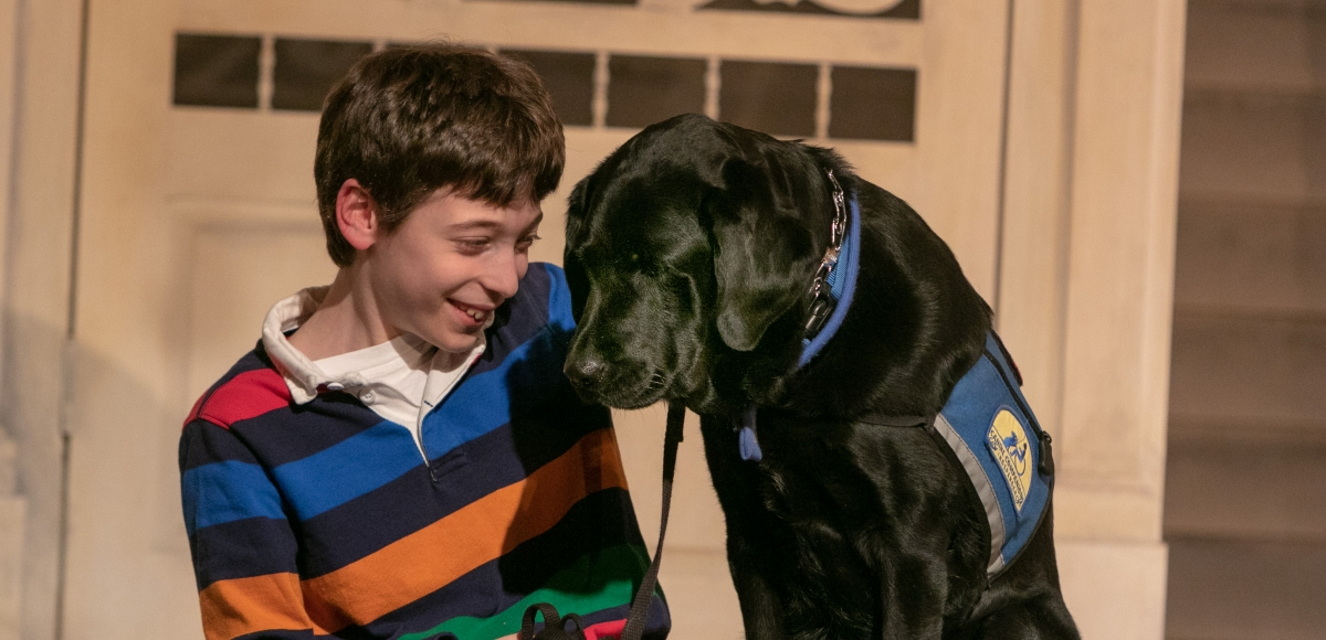 A young boy and a service dog in a performance of Healing Voices: Caregivers Stories Onstage