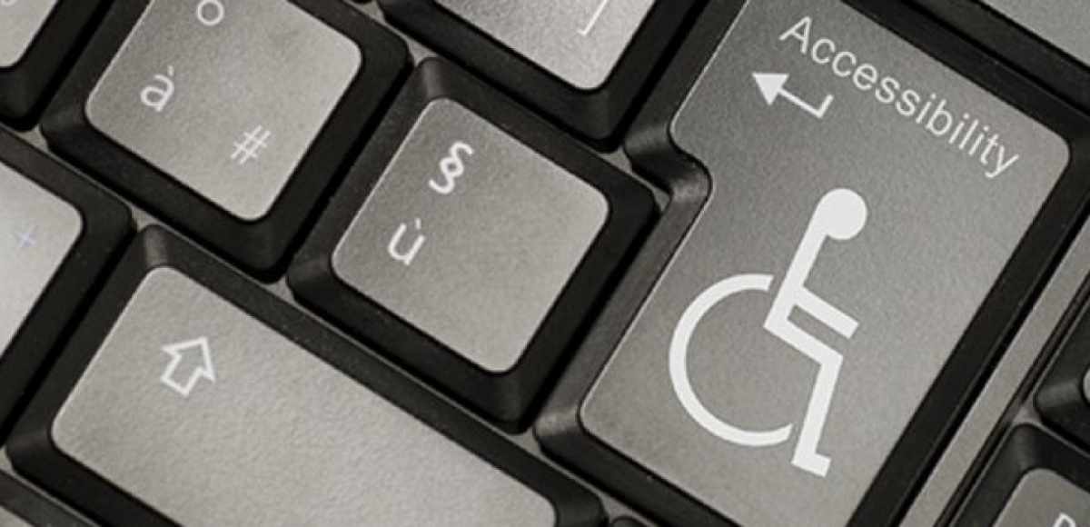 "Closeup of computer keyboard with wheelchair symbol on ""enter"" key"