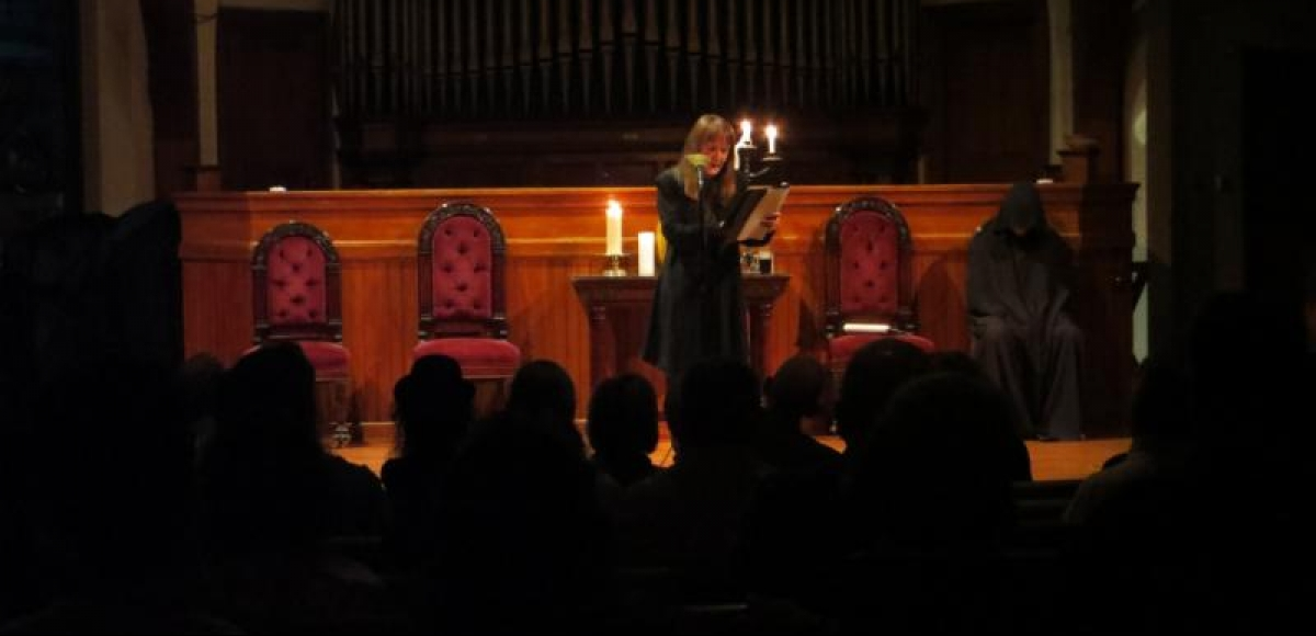 Gayle Stahlhuth reading a story by Poe with Lee OConnor in a hooded cape, ready to read next