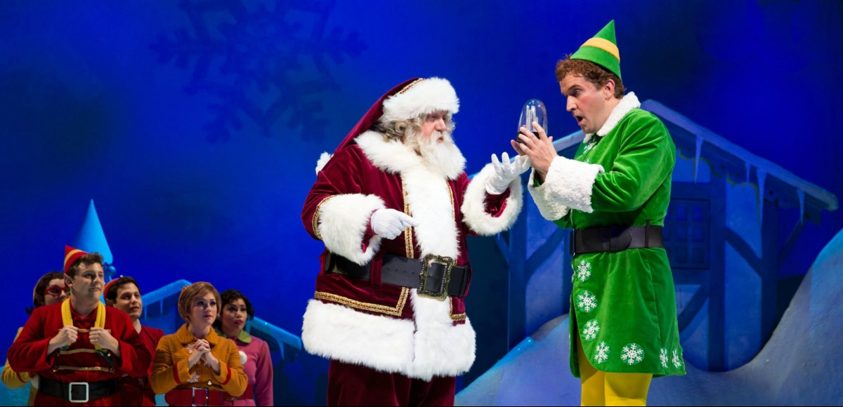Photo of Santa giving a snowglobe gift to Buddy the Elf