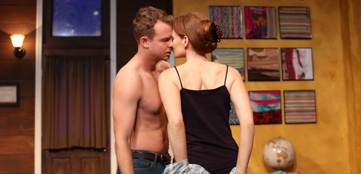 Actors passionately kissing on stage in a Centenary production.