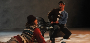 Two Actors, one lying on the ground, and one on a chair